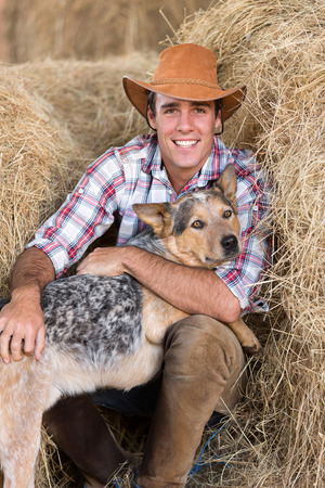 working cowboy: portrait of cowboy with his dog sitting on hay