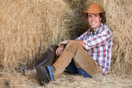 good looking american western cowboy sitting on hay