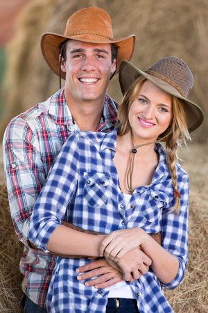 young farming couple hugging inside barn photo