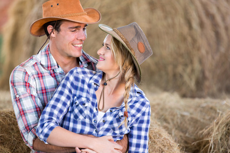 loving young american western couple hugging in barn photo