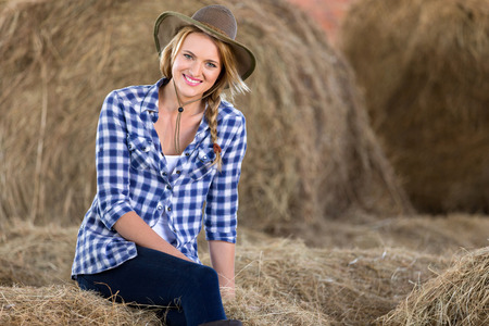 woman pose: attractive cowgirl sitting on hay bales in barn Stock Photo