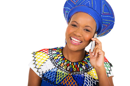 ethnic attire: pretty african zulu woman talking on smart phone isolated on white background Stock Photo