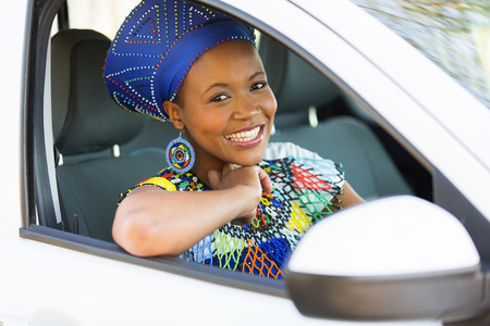 ethnic attire: attractive young african woman in traditional clothes inside a car