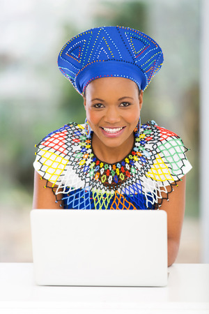 african fashion: pretty south african woman using laptop computer at home Stock Photo