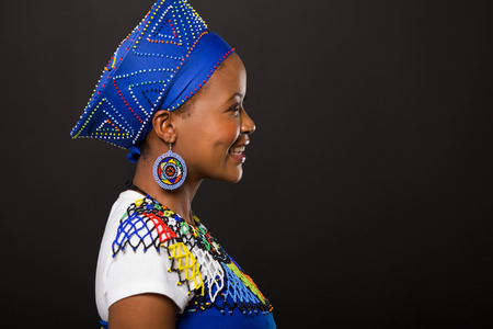 zulu: side view of young african zulu woman on black background