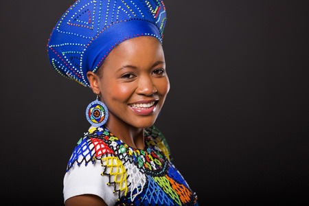 smiling zulu woman in traditional clothes looking at the camera on black background photo