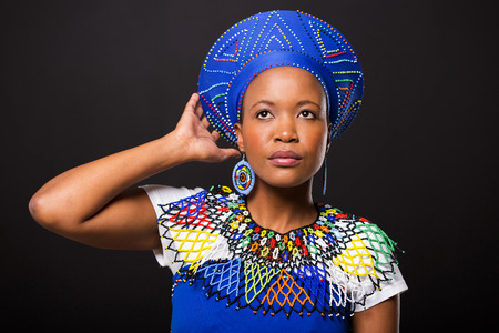 ethnic attire: attractive south african woman in traditional attire looking up on black background
