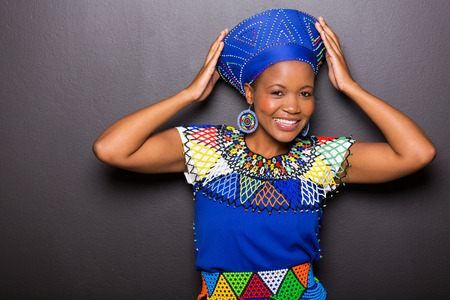 ethnic attire: beautiful african model in traditional attire posing on black background