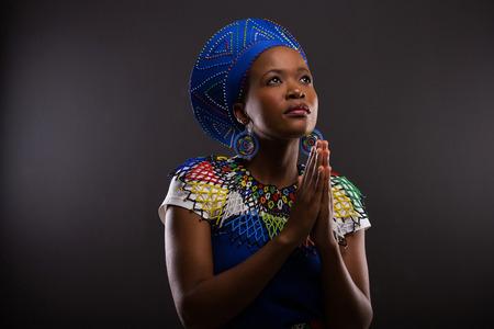 黒の背景上に祈って宗教若いアフリカ人女性