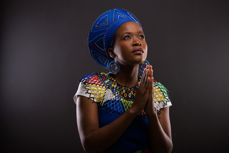 mujer rezando: joven mujer africana religiosa rezando sobre fondo negro Foto de archivo