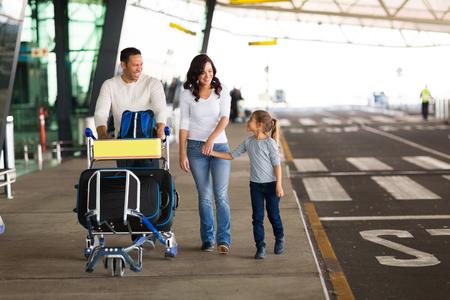 fröhliche junge Familie am Flughafen mit einem Wagen voller Gepäck