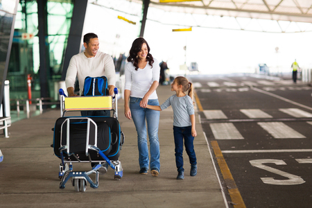 cheerful young family at airport with a trolley full of luggage Stockfoto