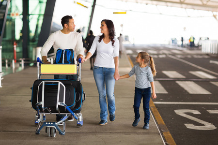 šťastná rodina cestování s kufry na letišti
