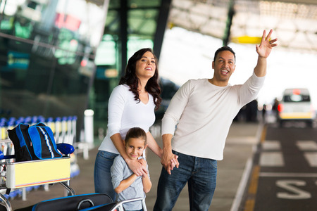 handsome man and his family hailing taxi at airport