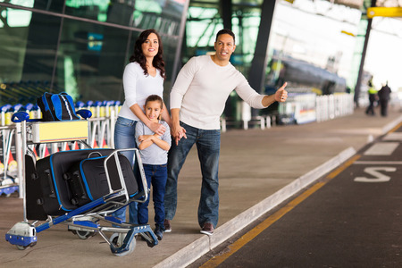 family hailing for a taxi after arriving at airport