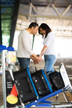 parting: caring man comforting his girlfriend before boarding airplane at air port