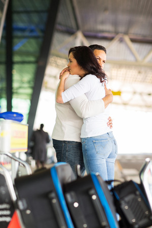 sad young couple say goodbye at airport photo