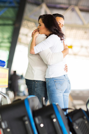 farewell: loving couple hugging deeply before parting at airport