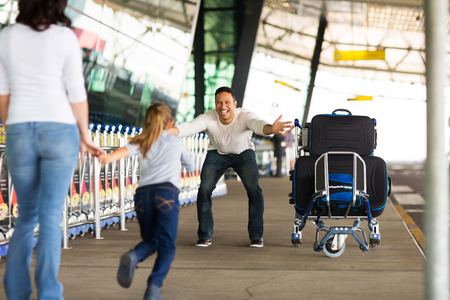 arriving: excited little girl running to her father at airport after a long wait with mother Stock Photo