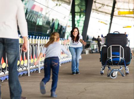 実行している彼女の母に空港で長い待ち時間の後に彼女の父親と一緒に若い女の子