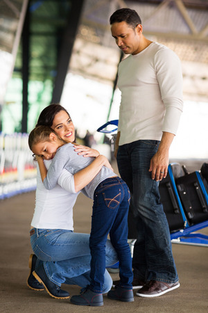 adult woman hugging her daughter at airport before departure Stock Photo