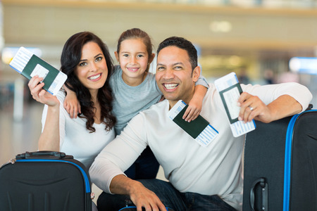 happy family holding boarding pass and passport at airport Stockfoto