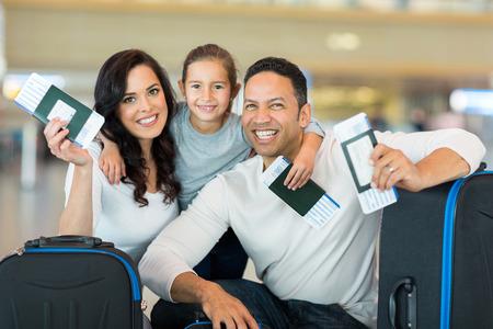 gelukkig gezin met instapkaart en paspoort op de luchthaven