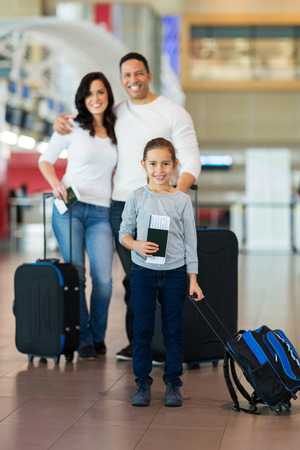 travelling: beautiful little girl travelling with her parents at airport Stock Photo