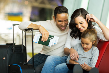 viaje familia: niña que usa la PC de la tableta con los padres en el aeropuerto a la espera de su vuelo