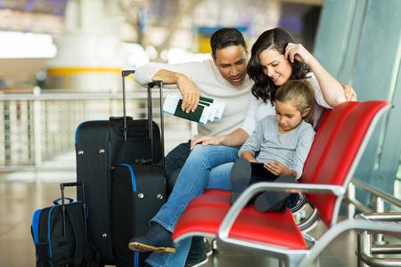 viaje familia: niña con los padres que usan el ordenador tableta en el aeropuerto a la espera de su vuelo