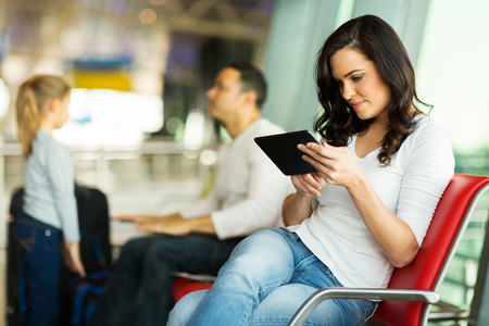 young woman using tablet computer at airport with family on background photo