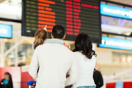 gente aeropuerto: Vista posterior de la ni�a con sus padres se�alando a la informaci�n de vuelo en el aeropuerto