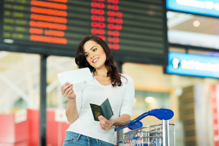 arrival departure board: smiling woman looking at air ticket in airport