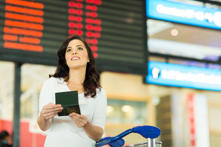 arrival departure board: gorgeous young woman checking flight information at airport
