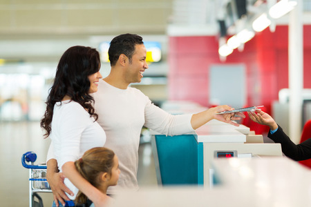 to check: cheerful family handing over air ticket at airport at check in counter Stock Photo