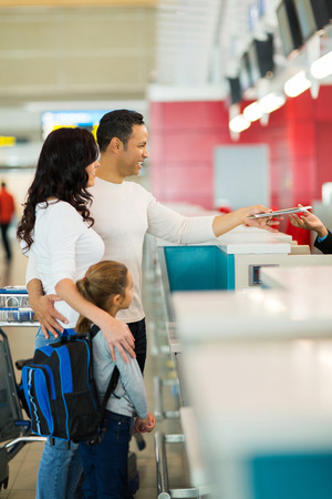airport check in counter: family checking in at airline counter in airport