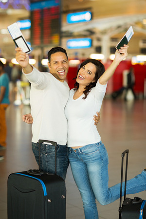 cheerful couple going on a holiday by air photo