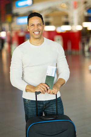 good looking man: good looking man traveling holding passport and boarding pass at airport Stock Photo