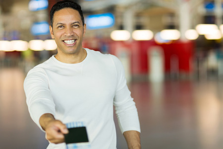 handsome mature man handing over air ticket at check in counter photo