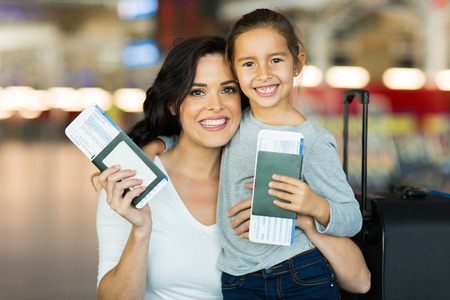 hermosa madre e hija con pasaportes y tarjetas de embarque en el aeropuerto