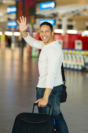 farewell: cheerful man waving goodbye at airport