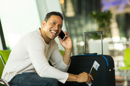 cheerful man talking on cell phone at airport photo