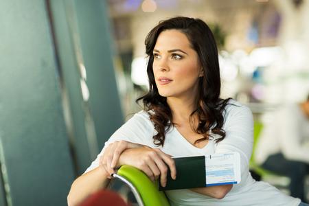 hübsche Frau wartet auf ihren Flug am Flughafen Standard-Bild