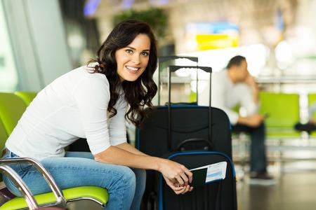 šťastná žena čekání na letu na letišti