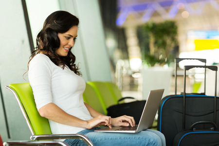 happy woman using laptop computer at airport photo