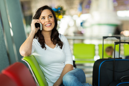 pretty traveller making a phone call at airport photo