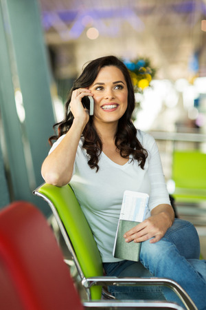 happy woman talking on cell phone while waiting for her flight at airport photo