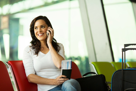 gorgeous woman talking on mobile phone at airport photo
