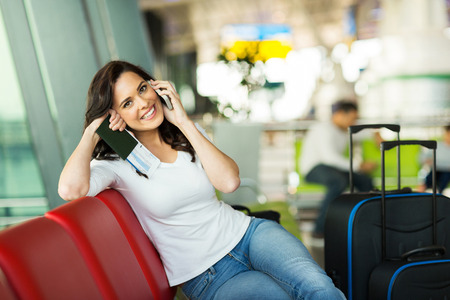 cheerful woman talking on cell phone at airport photo