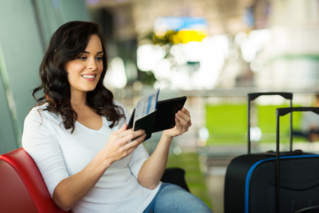 transportation travel: young woman reading her email on tablet computer while waiting for flight at airport